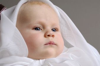 Infant dressed in baptism clothes.