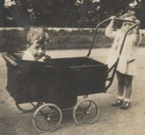 1930s Toddler pushes younger brother in pram.
