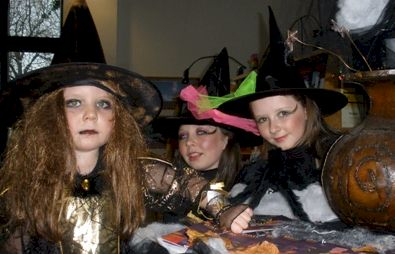 Three young girls dressed in Halloween costumes.