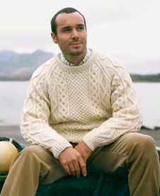Man seated on sea wall wearing cream coloured Aran knitwear