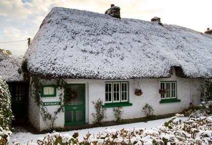 A traditional thatched cottage, whitewashed and with glossy mid-green painted woodwork, in Adare, Co Limerick, Ireland.