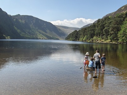 Waterside view of Glendalough's Upper Lake, hemmed in on three sides by high hills. In foreground is a group of four children, paddling in the shallows.