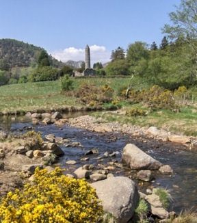 Distant view, across rocky stream and fields, to the medieval Round Tower at Glendalough, Co Wicklow.