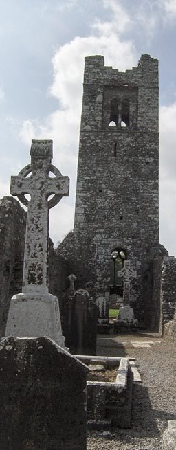 Ruin of Slane Abbey in Ireland with newer celtic cross in foreground.