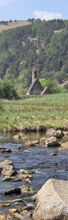 View of St Kevin's church at Glendalough in mid-distance, across rocky river and fields, with mountains and sky as backdrop.