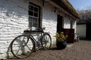 Whitewashed thatched cottage with vintage bike propped against wall.