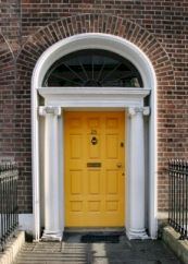 Smart Georgian-style door in Dublin, with fan-light above. Door painted a bright yellow.