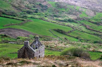 Hilly landscape in Ireland with patchwork fields and a house ruin in the near-view.