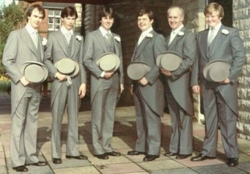 A father with his five young adult sons, all dressed in grey 'top hat and tails' wedding outfits, pose outside church.