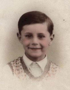 Hand coloured head-and-shoulders photo of young (8-year-old) boy, end of 1930s, London.
