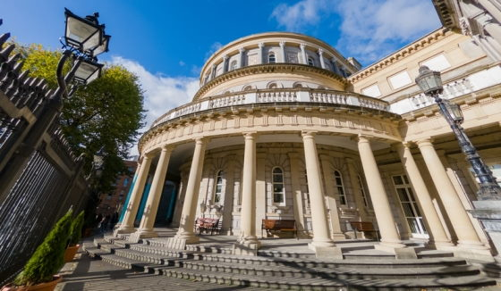 Wideangle view of National Library of Ireland in Dublin, focussing on stone steps and columns of entrance, dome of the Reading Room and wrought iron railings and street lamps.