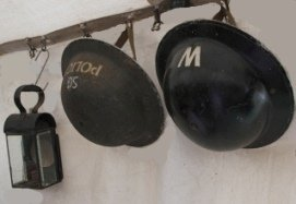 WWII helmets and lantern hanging on wall.