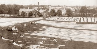 Vintage photo showing strips of linen being laid out in the fields (known as Bleaching Greens) surrounding an old mill in Co Antrim